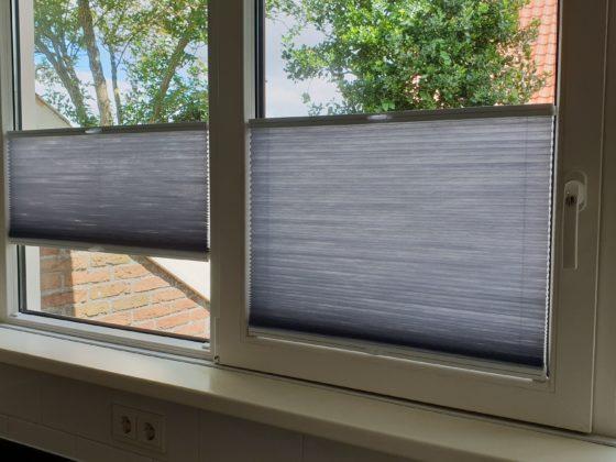 Plisse gordijn in het raam